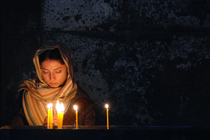 woman praying with lit candles